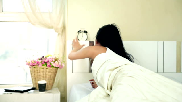 Angry woman lying a bed and holding an alarm clock