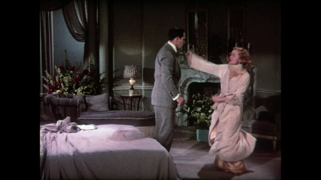Angry woman (Carole Lombard) punches man (Fredric March) in the face, knocking him out cold