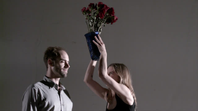 Angry woman smashing vase on man's head