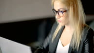 Böse junge Frau, die bis spät abends im Büro arbeiten