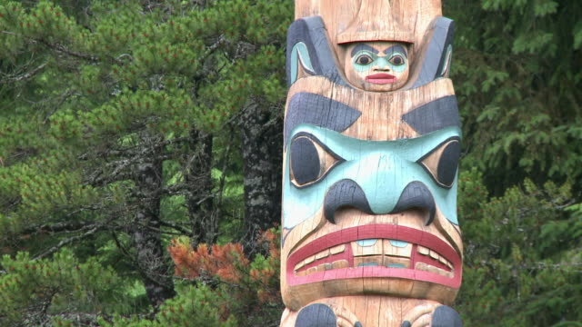 'CU of animal face on brightly painted totem pole, evergreen trees behind, near Ketchikan, Ketchikan Borough, Alaska.'