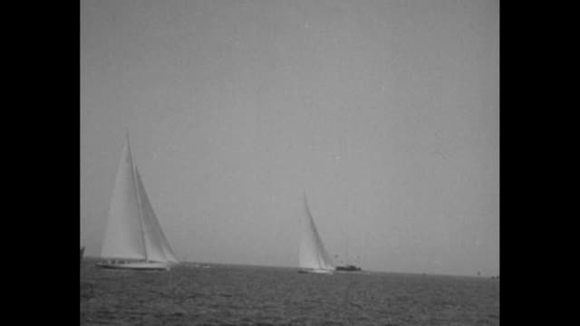 Animated titles 'News Flashes' with iris shot / yachts with majestic sails slice through ocean waters ship with lifeboat stands by