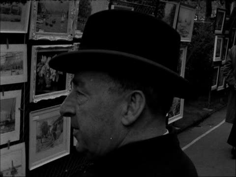 Annual painting exhibition on the Victoria Embankment ENGLAND London Victoria Embankment People including a policeman looking at paintings Painting...