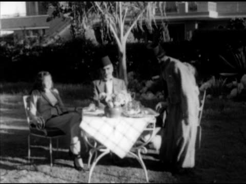 Anonymous middleaged wealthy landowner sitting outside w/ family Turkish wife daughter speaking to brown skin servant NO SOT MS Servant Lighting...