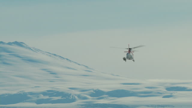 Antarctic research helicopter flies towards distance icefield
