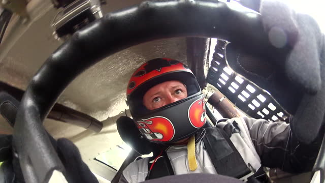 A stock car driver turns a steering wheel 180 degrees.
