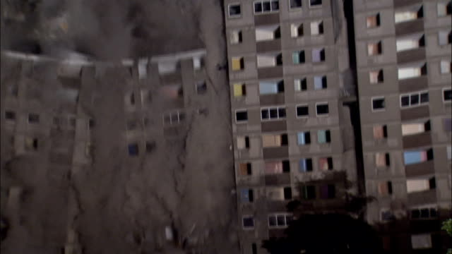 MS CU  Apartment building is demolished in controlled implosion using explosives and dissappearing cloud of dustin night / Sighthill, Scotland, UK