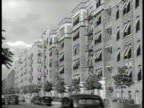 Apartment buildings line doublewide road w/ center trees WS Apartment buildings Women setting table in small apartment HOUSES Rows of small houses...