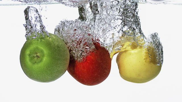MS SLO MO Apples entering into water against white background / Vieux Pont, Normandy, France