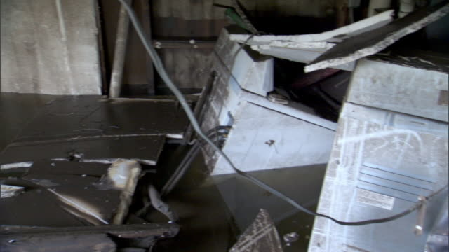 Appliances and other debris float in a flooded basement.