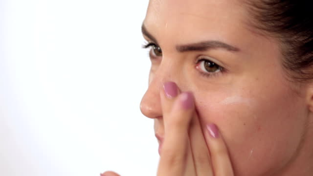 Applying moisturiser into face