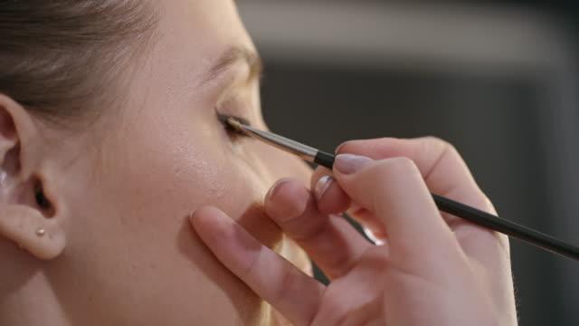 Applying winged eye-liner on female model