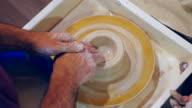 Leerling modellering van klei pot op aardewerk wiel