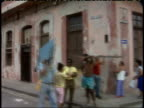 April 1 1994 MONTAGE Passing by residents and pedestrians in urban area of rundown buildings and structural ruins / Havana Cuba