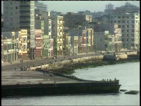 April 1 1994 WS Tightly knit row of pastel colored buildings lining coastal boulevard with vehicle and pedestrian traffic / Havana Cuba