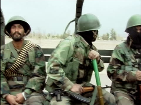 April 2004 armed ANC and US special operations forces soldiers riding in back of open truck outside Kandahar / pan to soldiers in truck wearing...