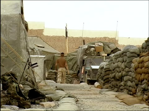 April 2004 soldiers walking past stockpiles at Camp Tiger / zoom out to view of US flag blowing over stockpiles / Ghazni Afghanistan