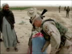 April 2004 US Army Major Wes Parker of 486th Civil Affairs Battalion and US soldier bringing blankets to Afghan villagers in Kandahar Province...