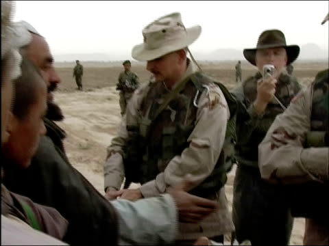 April 2004 US Army Major Wes Parker of 486th Civil Affairs Battalion shaking hands with Afghan villagers after donating blankets / Kandahar Province...