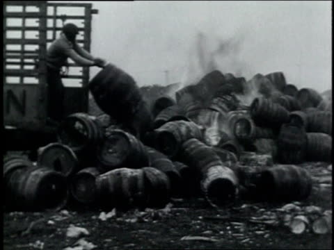 April 28 1932 MONTAGE federal agents throwing barrels of whiskey and kegs of beer onto a large fire / Newark New Jersey United States