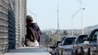 April 9 2009 WS ZI Man sitting by fence beside row of cars waiting at Mexican and US border Juarez Chihuahua Mexico AUDIO
