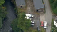 Aerials of Machynlleth WALES Powys Machynlleth of local area including countryside woodland river houses parked police vehicles police officers along...