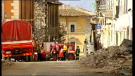 L'Aquila earthquake aftermath Rescue crews and rubble on road narrow roads of town lined with rubble and partially damaged roof of tall building