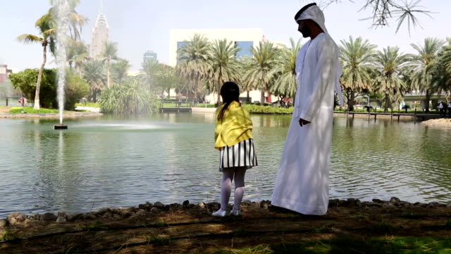 Arab father playing with daughter in picnic near lake