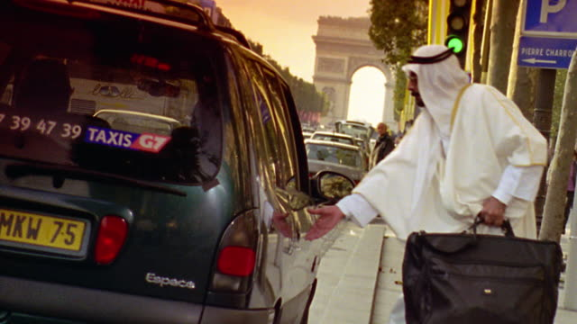 CANTED Arab man in robes with luggage entering taxi on Champs Elysee with Arc de Triomphe in background