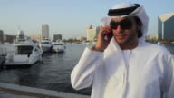 CU MS ZO ZI Arab man in traditional dish dash at Dubai Creek using mobile phone / Dubai, United Arab Emirates