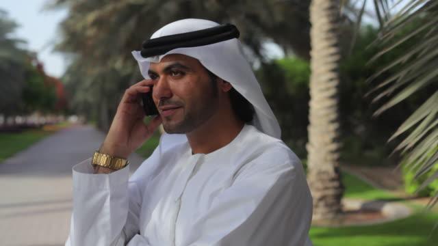 CU Arab man in traditional dish dash using mobile phone / Dubai, United Arab Emirates