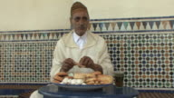 MS Arab man wearing jellaba eating pastry, drinking tea and paying bill, Rabat, Morocco