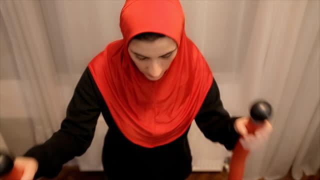 Arabische vrouw is training op een sport-oefening machine thuis