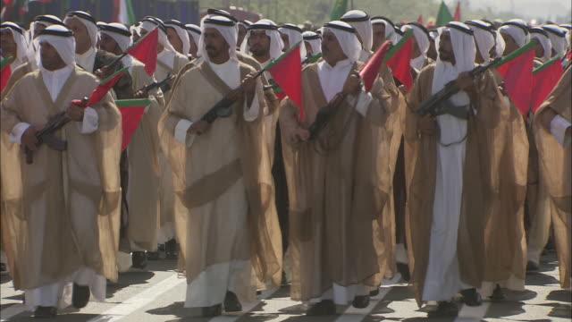 WS ZO ZI PAN Arabian men in parade holding rifles with red triangular flags / Tehran, Tehran Province, Iran