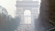 Arc de Triomphe in Place Charles de Gaulle at western end of tree lined Avenue des ChampsElysees filled w/ cars traffic in smog air pollution Global...