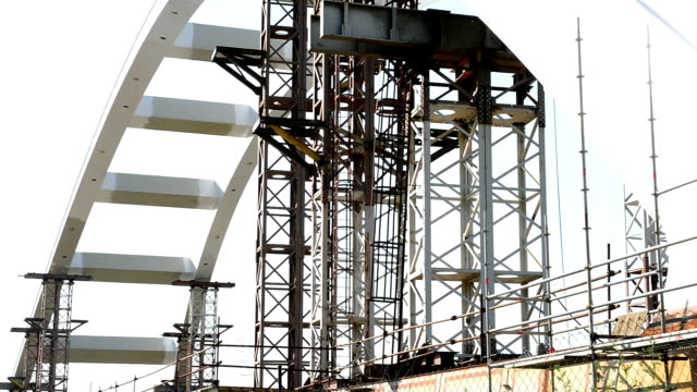 Arch bridge construction near railway lane and building bars