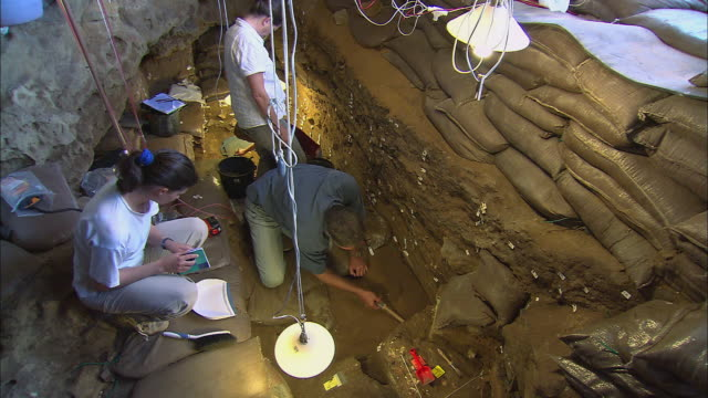 TD Archaeological researchers examining fossils and findings within the Blombos Cave / South Africa