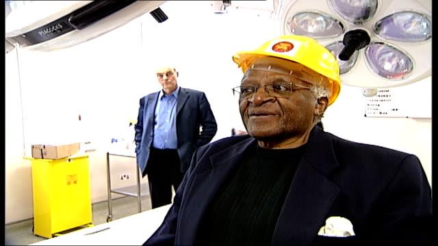 Archbishop Desmond Tutu visits St Luke's Hospital in London Tutu wearing safety helmet posing for photocall in front of medical equipment Tutu...