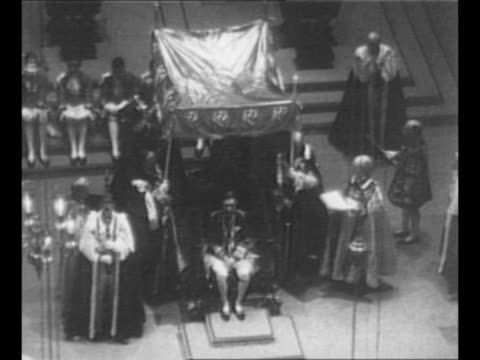 Archbishop of Canterbury places King Edward's Crown on George VI's head during coronation ceremony at Westminster Abbey / persons in the Royal Box...