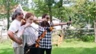 Bogenschießen in den Hinterhof. Zwei Teenager Gilrs, Schwestern, schießen zusammen. Pennsylvania, Poconos, USA