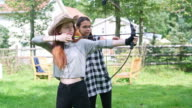 Archery at the backyard. Two teenager gilrs, sisters, shooting together. Pennsylvania, Poconos, USA
