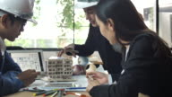 Architect and colleague constructing an architectural model