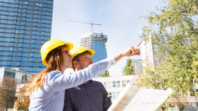 MS architect and contractor discussing building plans in front of high rise construction