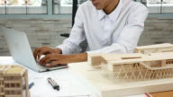 Architect Checking on his architectural model with Laptop