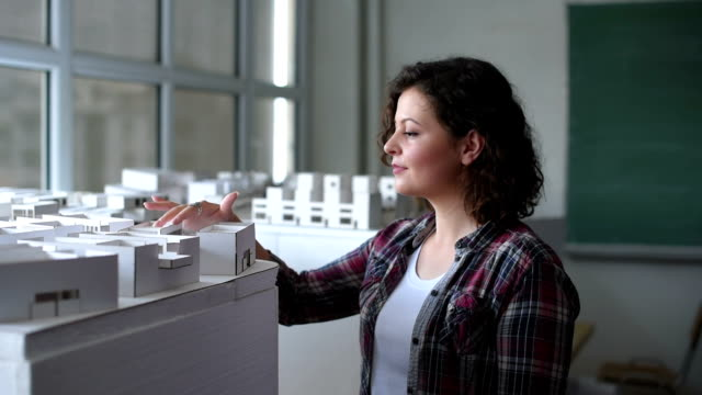 Architect constructing an architectural model in office