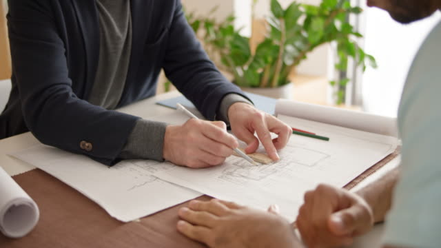 Architect consulting about the plans he made with a young family in their home