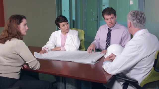 Architect Discusses Blueprints with Doctors and Managers