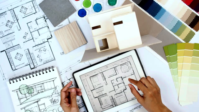 Architect & interior designer working at worktable with home model, tablet, blue print