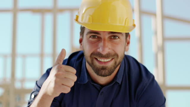 Architect looking at camera and showing thumbs up at construction site