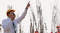 Architect talking on a Walkie-Talkie in the construction site, Delhi, India